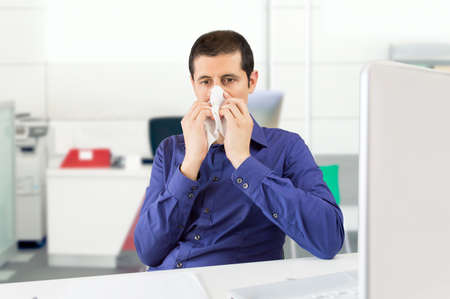 cold season: sneezing businessman sick blowing nose at the office Stock Photo