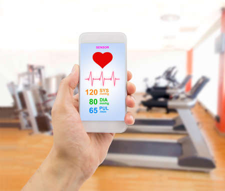 wacom: hand holding the smartphone with an app health sensor with the gym in background. The screen content is designed by me and not is copyrighted by others and created with wacom tablet and PS