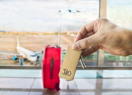 hotel chain: guest holding the hotel room key isolated at the airport