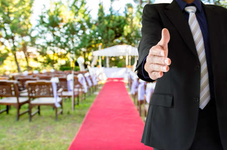 Primer plano de un apretón de manos en la boda de jardín de un organizador de eventos y planificador de la boda Foto de archivo - 51495707