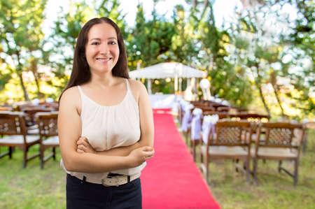 Hochzeitsplaner Frau ist die Hochzeit Empfang Veranstaltungsort für ihre Kunden die Organisation bei der Hochzeit Ort stehen und lächeln