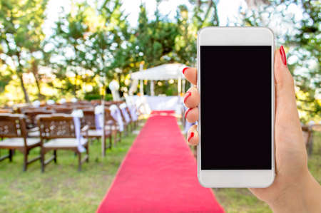 wedding celebration: hand with a phone with a background of a wedding Stock Photo