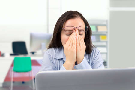 eyestrain: business woman with a eyestrain at the workplace
