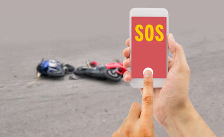 emergency number: hand holding a cellphone with emergency number SOS on the screen with a motorcycle accident in background