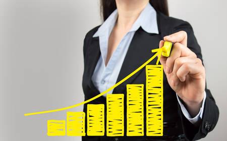 grafica de barras: Recortar foto de una mujer de negocios dibujar un gr�fico de crecimiento de los beneficios Foto de archivo