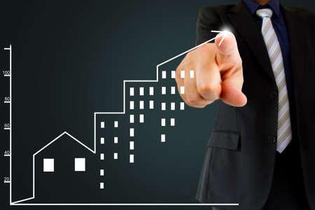 Geschäftsmann ist mit schwarzem Hintergrund, die eine positive Entwicklung der Immobilien-Investment Konzept. Standard-Bild - 52067987