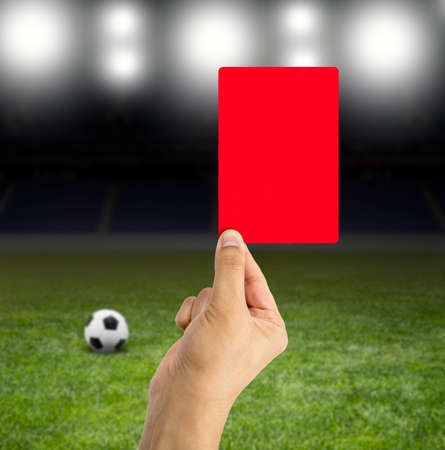 focuses: Football referee showing you the red card in a stadium under the bright focuses
