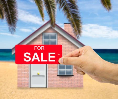 man holding card: Man holding card home For sale sign red label with percent sign in hand with sale concept and beach house background Stock Photo