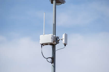 transponder: Antennas of mobile cellular systems with wifi hot spot repeater and cloudy blue sky Stock Photo