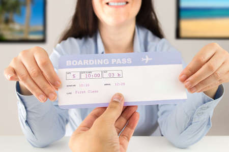 travel agent delivering the flight ticket to the customer at the travel agency