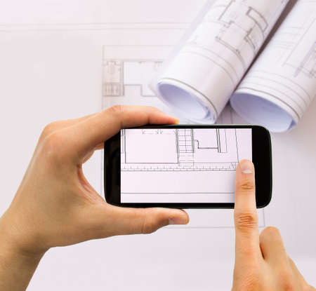 corporate espionage: businessman taking photo of plans with smartphone in connection with industrial espionage Stock Photo