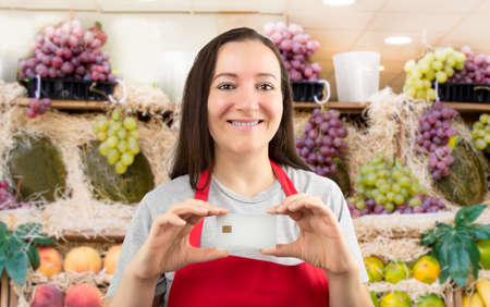 saleslady: smiling shopwoman showing credit cart with copy space at the fruit shop