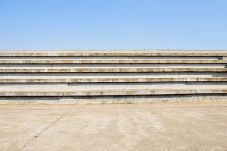 cement bleachers seats in an urban with blue sky background in sport centre Stock Photo
