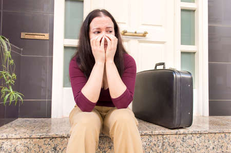 evicted: portrait of woman crying at the doorway with a suitcase as concept of divorced woman