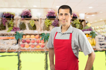 smiling shopman at the greengrocer with copyspace