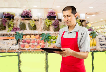 greengrocer: shopman in the greengrocer and fruit shop uses a tablet
