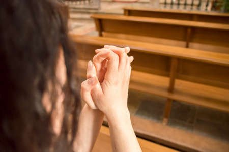 joined: detail of woman praying in a pew at a church with joined hands