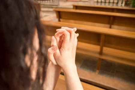 manos unidas: detalle de la mujer que ora en un banco en una iglesia con las manos juntas