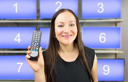 channel surfing: Closeup of a woman holding a remote control with channel numbers in background