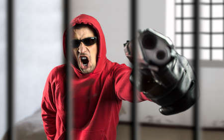 threatening: gangsman with gun in a threatening tone at the cell of a prison