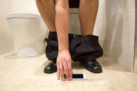 defecating: businessman lost smartphone while working in the wc