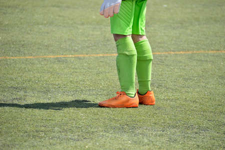 uniform green shoe: Cropped shot of a young boy foot on a soccer