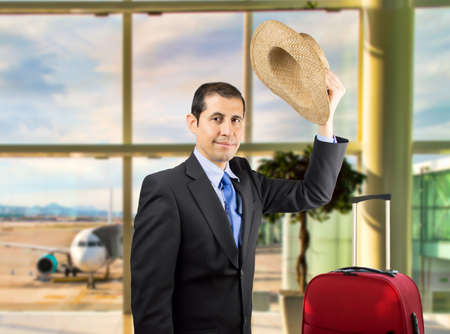 salutation: businessman is saying goodbye making a salutation with a hat on the hand on the airport