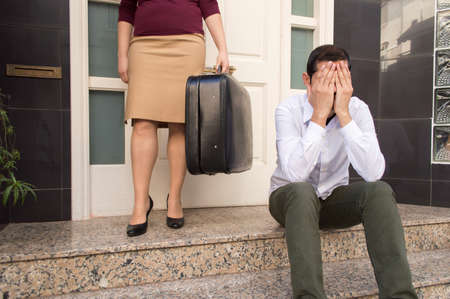 friendless: man expelled of home sitting and weeping and the wife holding the suitcase of husband in background at the doorway as concept of divorce Stock Photo