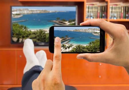 personas viendo television: Relajado hombre con el teléfono inteligente conectado a una televisión y previendo fotos en redes (imagen Teléfono de la TV y de una foto de una playa en Barcelona a partir de mi cartera)