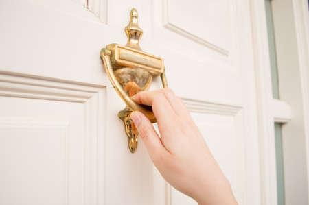 tocar la puerta: mujer que sostiene en la puerta utilizando la puerta de golpe de edad Foto de archivo