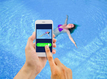 クリスタル ブルーの水に彼女の背中に浮かぶおよびスマート フォンでインターネットのソーシャルネットワー キングへのアップロードのカラフル