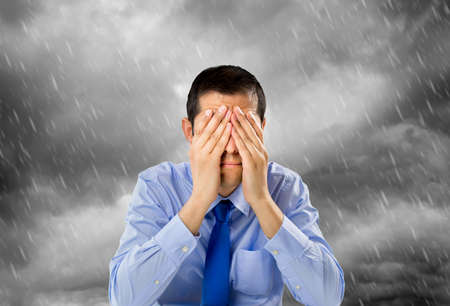 rain wet: portrait of businessman worried with hands on his face and the storm in the background