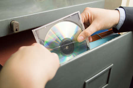 investigative: businesswoman keeping a backup of documents in a file cd in cabinet