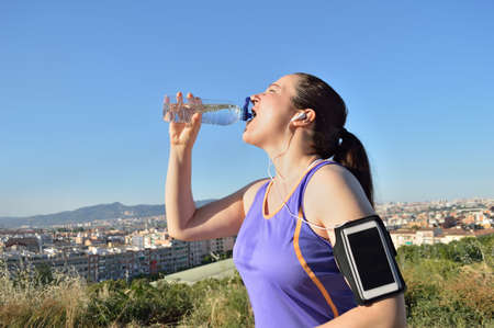 sportwoman: sportwoman drinking water at the park and city background