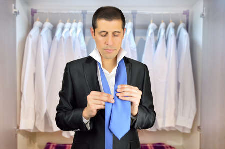 formal dressing: businessman adjusting his tie with a wardrobe in background