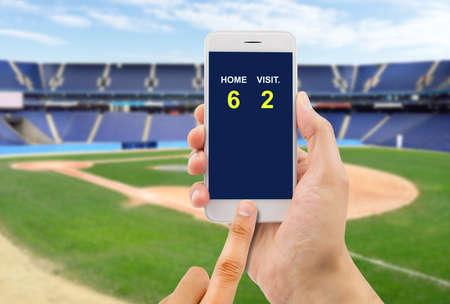 betting man through his smart phone in a baseball stadium Stock Photo