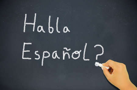 kiddy: Spanish language learning concept image. boy or student writing habla espanol on blackboard