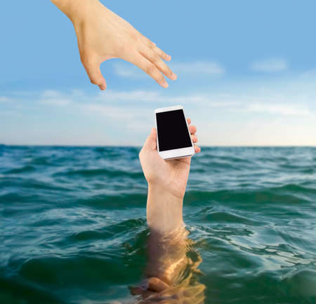 man who rescues the phone of a person who is drowning in the sea