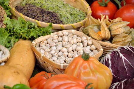 group of exotic vegetables as lettuce tomatoe red cabbage pepper alfalfa sprouts soysprouts with fruits as lychees and legums as chickpeas at the greengrocery on baskets Stock Photo
