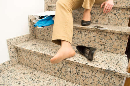 tripped: detail of woman with stilettos falling down with shopping bags on stairs Stock Photo