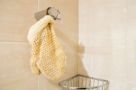 exfoliating glove hanging on shower at the bathroom with copyspace