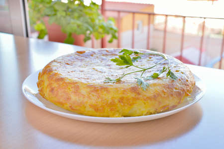 spanish onion: spanish omelette with eggs potatoes and onion with parsley leaf on the top over a wooden table at the terrace