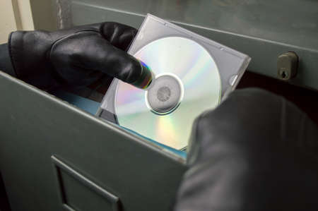 corporate espionage: thief stealing in a digitized office files in  compact disk
