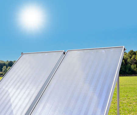 solar panels on a green meadow with blue sky background Stock Photo