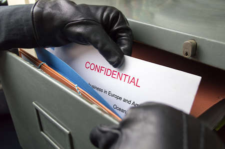 corporate espionage: thief stealing confidential files in an office