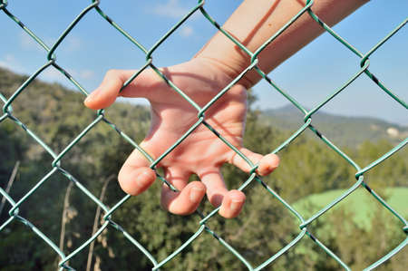 salto de valla: hand of an illegal emigrant jumping a fence on the border Foto de archivo