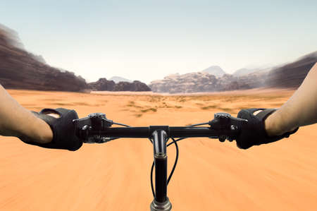 closeup of hands of a mountain biker at high speed on the desert in Jordan Stock Photo