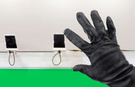 Closeup of a hand of a thief stealing a phone in a store