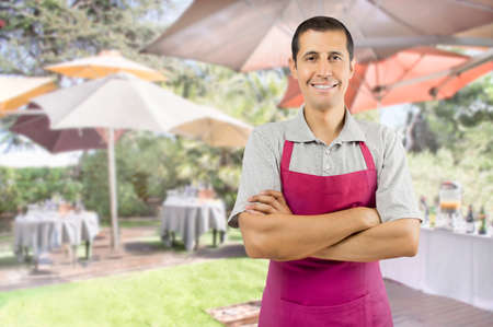 portrait of a happy waiter of catering with crossed arms standing at the terrace restaurant