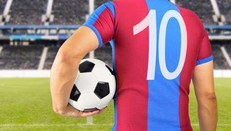 Cropped rearview image of a young man holding a soccer ball under his arm at the football stadium in barcelona